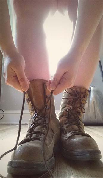 Bare legs and arms of a woman tying laces of heavy duty work boots.