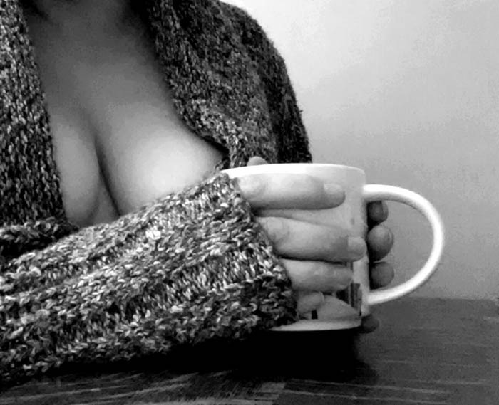 A woman in a sweater holds a hot cup of tea.