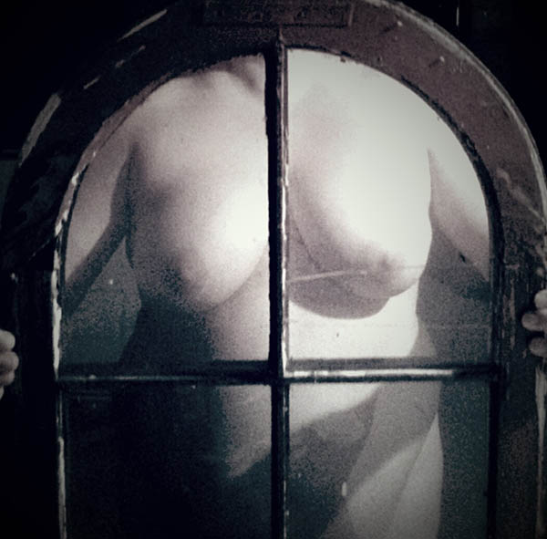 A nude woman holding an arched window in front of her body.