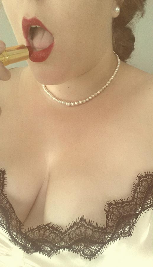 A woman in a negligee and pearls applying red lipstick.