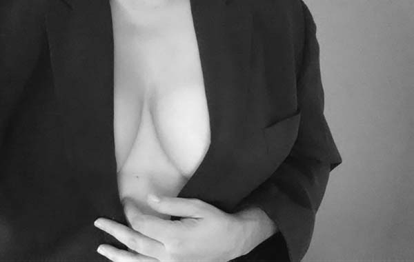 Woman's torso wearing a black men's suit jacket, holding the front closed with one hand.