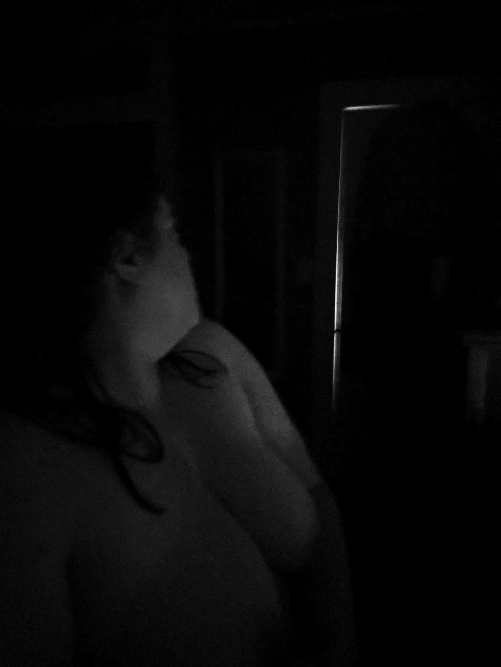 nude woman turns to face door in dark room