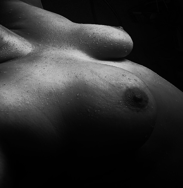 black and white photo of breasts covered in water droplets