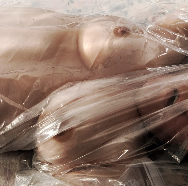 color photo of open-mouthed nude woman wrapped in a plastic sheet
