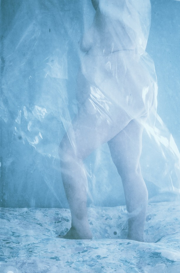 blue tinted photo of nude woman standing with plastic sheet floating around her